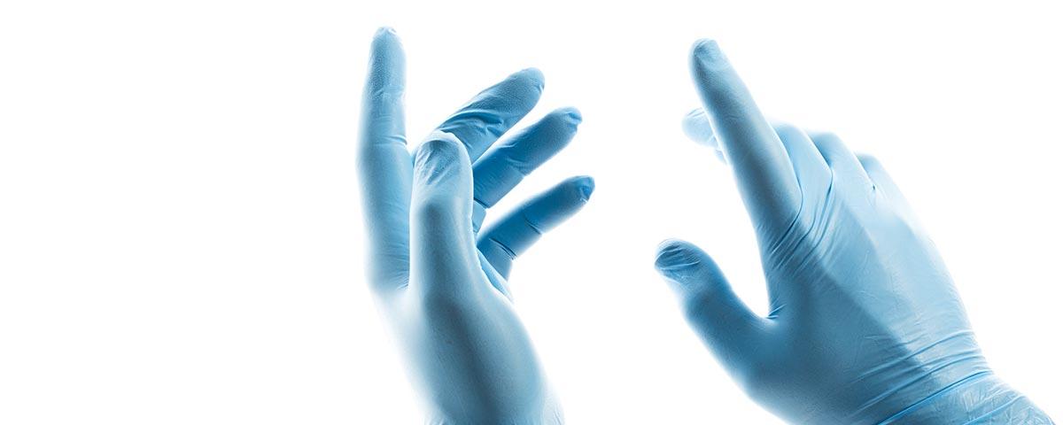 Zwei Hände in blauen Einweghandschuhen